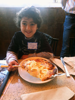 Sky Masori samples pizza he learned to make at Kavod Elementary School playdate