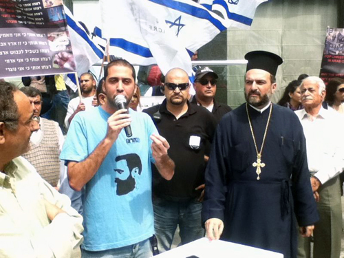 Father Gabriel Nadaf at right appears at rally calling for the West to protect Christians in Islamic countries