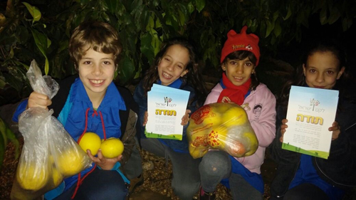 Israeli children with certificates and bags of fruit picked for distribution to the needy