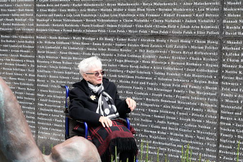 Survivor Agathe Ehrenfried visits wall at Lawrence Family JCC where names of some of her family members who perished are listed.
