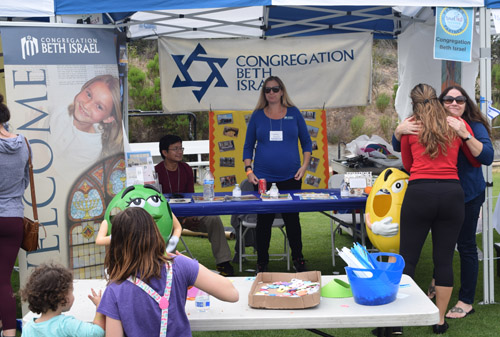 Congregation Beth Israel distributed M&Ms to the children, and information to adults. Van Khoth and Bethany Eisenberg were behind the table as Cathy Goldberg received a hug from a friend.