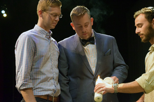Bill Jefferson and Kevin Nill light a candle to memorialize gays murdered during the Holocaust. At right, Alex Schindler assists.