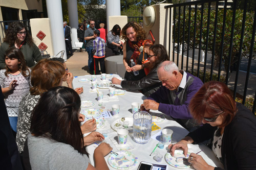 Attendees at Holocaust commemoration paint butterflies as artist Cheryl Rattner price in background observes
