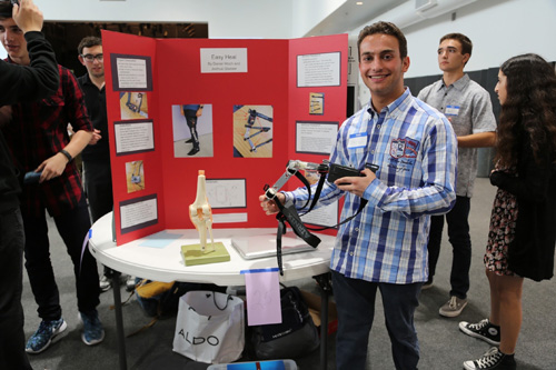 A Student of San Diego Jewish Academy stands with his group's project at the CIJE-Tech Young Engineers Conference hosted by Shalhevet High School in Los Angeles. The CIJE Tech High School Engineering Program is provided by the Center for Initiatives in Jewish Education (CIJE).