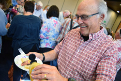 Bill Sperling, president of the Tifereth Israel Synagogue Men's Club, adds a little mustard to a temperately sized sandwich