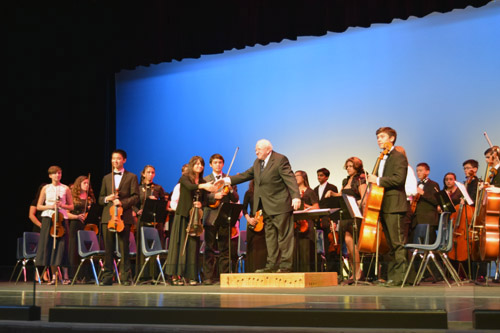 David Amos acknowledges applause after conducting the PHHS orchestra. Third from left is violin soloist Kalos Chu.
